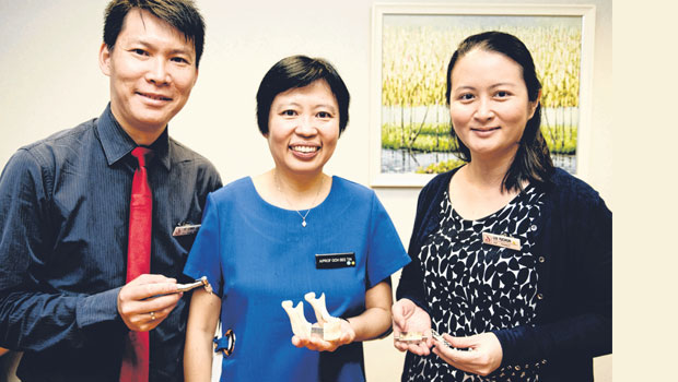 (from left) Dr Edwin Liu, Dr Goh Bee Tin and Dr Liu Yuchun with a mock-up of the new device. ST PHOTO ALVIN HO
